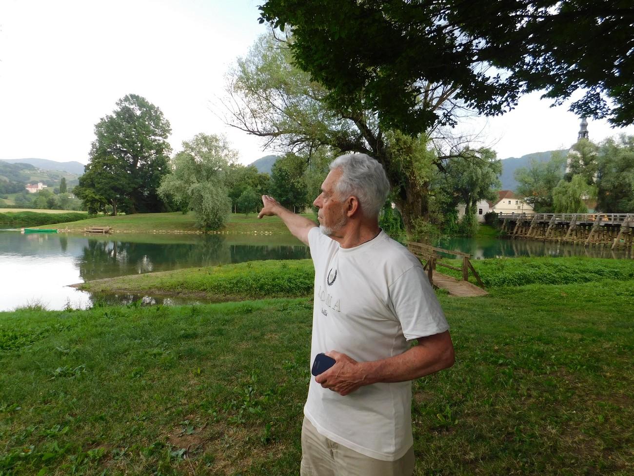 Pričevalec Jože Jankovič stoji na levem bregu Krke v Kostanjevici, ki je bil nemški. Mejna kontrola je bila na severni strani mostu, ki je na desni strani slike. V delu Jankovičeve hiše na otoku je bil italijanski bunker. Avtor fotografije: Božidar Flajšman.