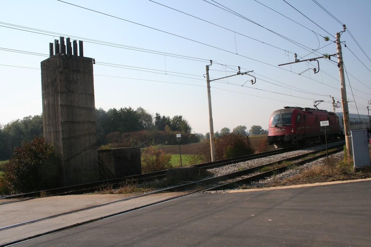 Ob železniški progi v Dobovi stoji visok betonski blok, vanj so zabetonirane tudi tračnice. Poleg je še ena manjša konstrukcija in med tiroma še nizek betonski blok. Vse so zgradili Nemci med vojno, če bi bilo potrebno onesposobiti promet. Miniranje bi uničilo progo, minirane betonske konstrukcije pa bi zasule progo in še otežile rekonstrukcijo. Avtor fotografije: Božidar Flajšman.
