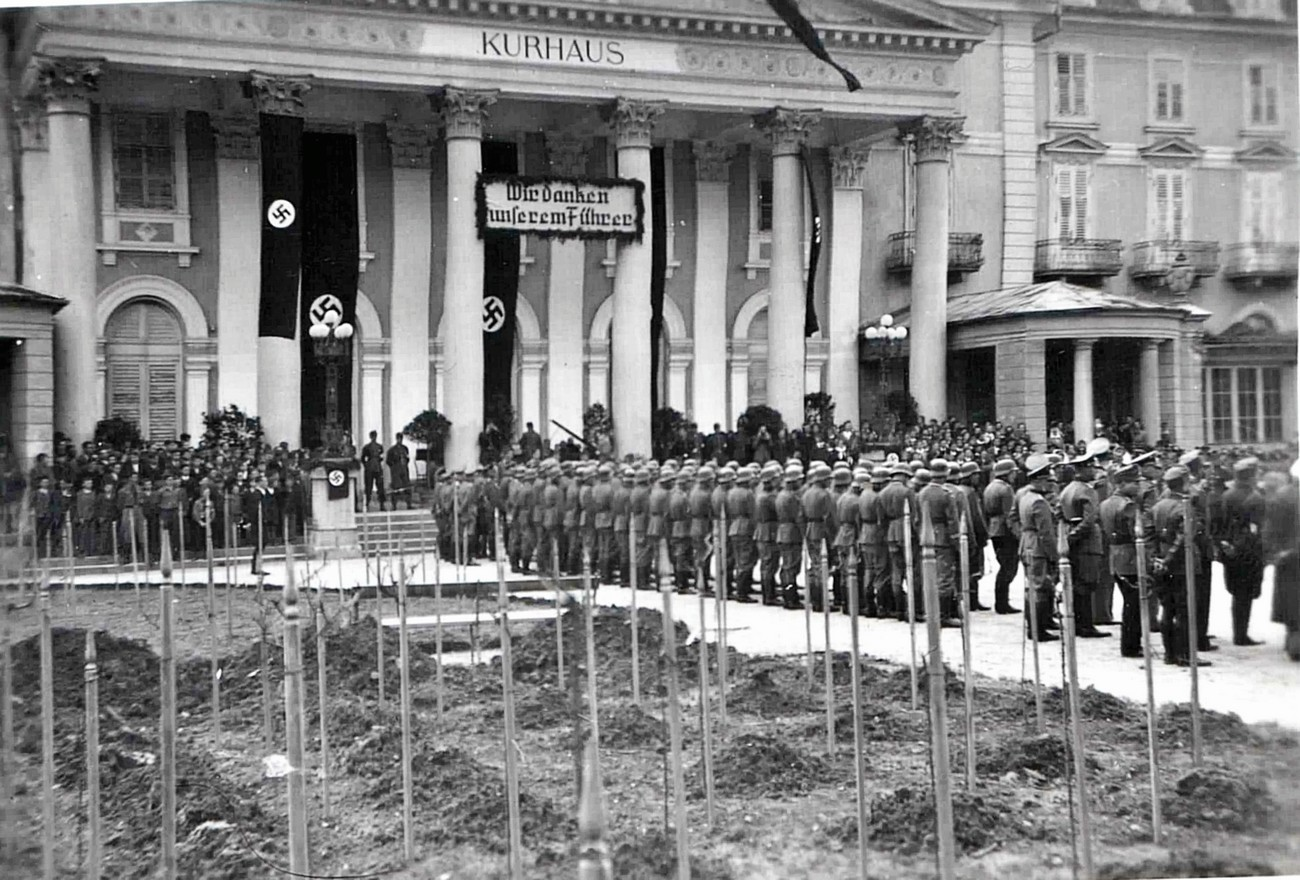 """A troop of 60–70 German soldiers lined up on 11 April 1942 in front of Zdraviliški dom [Health Resort Hall] in Rogaška Slatina, where a solemn celebration was held on the first anniversary of the German """"liberation"""" of this resort town. Standing in the background, on the far left and right are boys from the Hitler Youth, who had rooms in the Pošta Hotel. Standing between them are Wehrmannschaft units. Source: School chronicle of the Kostrivnica Primary School."""