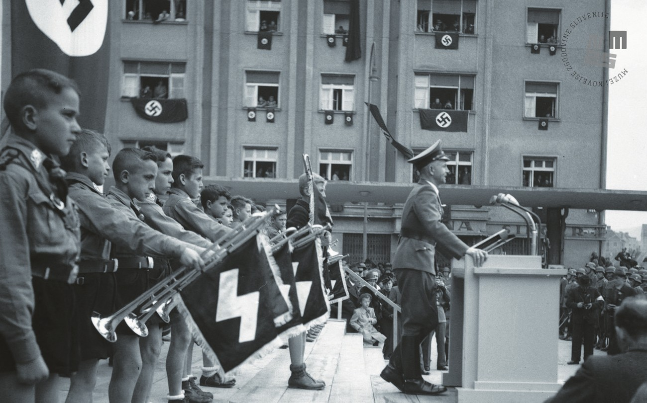 Immediately after occupation, Germans began the complete Germanisation of the population of Lower Styria. The photograph shows a celebration involving German organisations, such as the German Youth (Hitlerjugend), etc. The entire surrounding area bears Nazi symbols. MNZS.