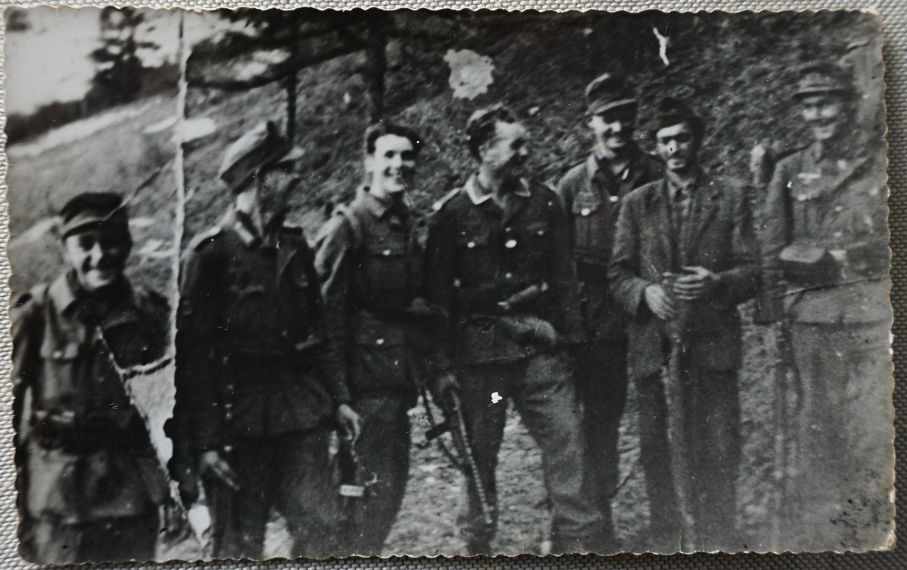 3. decembra 1943 je bil del Gradnikove brigade nastanjen na kmetiji pri Mrzlikarju nad Otaležem, ko jih je nenadoma presenetila kolona 150 Nemcev iz Idrije. Mrzlikarjev kozolec je začel goreti, med člani Gradnikove brigade pa je nastala velika zmeda. Več deset borcev je bežalo v smeri proti nekdanji italijansko-nemški meji, utrjeni z žičnimi ovirami in minskimi polji, od koder so se kmalu zaslišale močne eksplozije. Za velik del od 37 padlih tistega dne so bile usodne prav smrtonosne obmejne ovire. Fotografija prikazuje pri napadu ujetega partizana, ki so ga Nemci nato odvedli v Idrijo. Fotografijo hrani Aleksander Eržen.