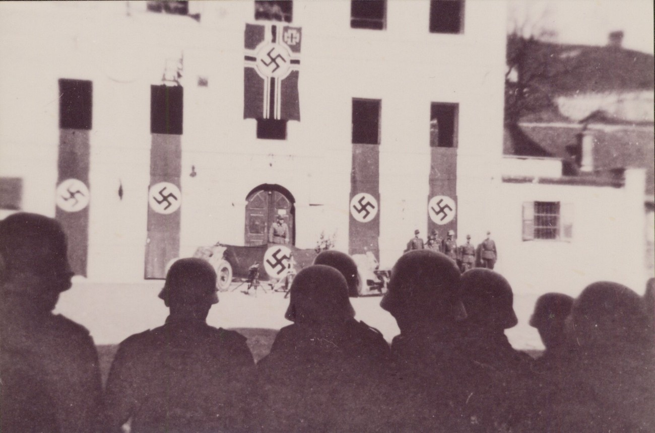 German military formation in Idrija's main town square. Between 1943 and 1945, German Nazi flags replaced the Fascist bundle of sticks on top of the former restaurant Pri črnem orlu. The photograph was taken during the celebration of the Day of the Wehmacht in 1943. Author (presumably): Peter Weissbacher, partly colorized. Idrija Municipal Museum.