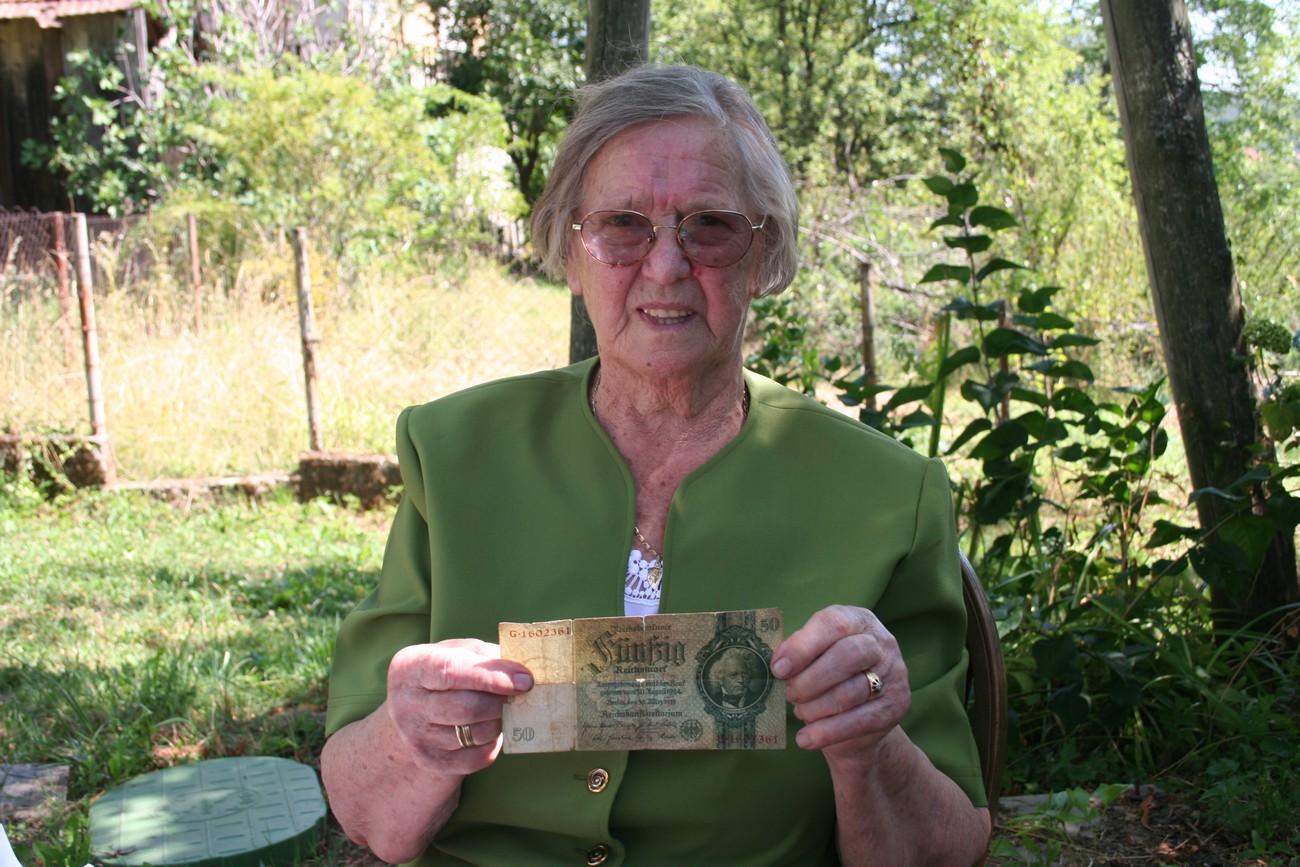 Danica Car iz Brezovice še vedno hrani bankovec za 50 »reich« mark, poklonil ji ga je ranjeni nemški vojak, ki so ga tudi zdravili v partizanskih bolnišnicah na Žumberku. Avtor fotografije: Božidar Flajšman.