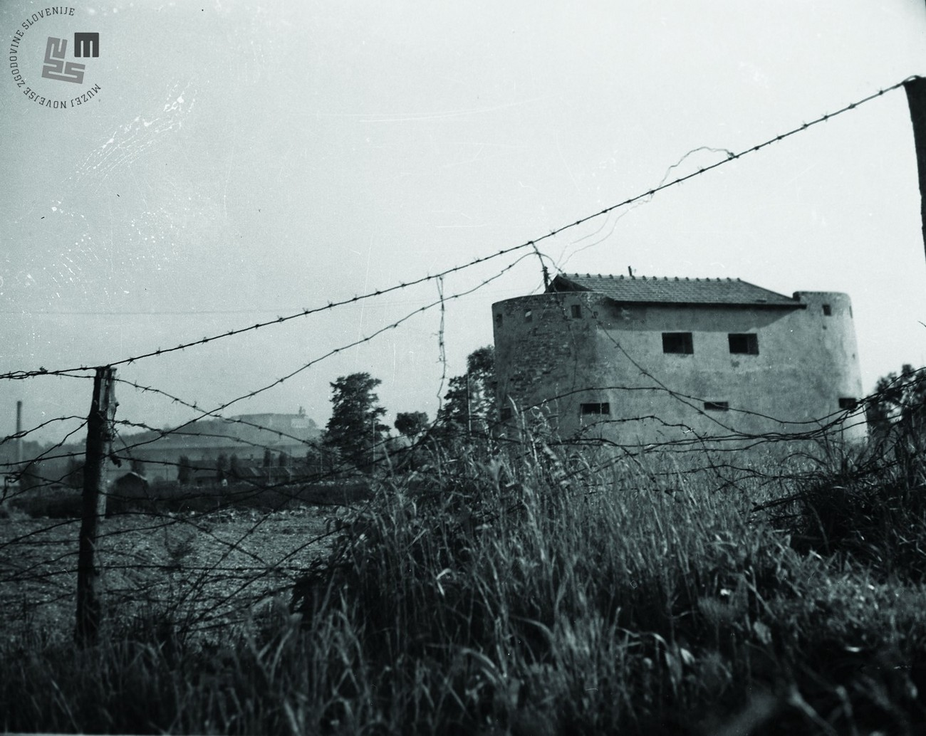 Wire around the defence bunker close to the erstwhile Evangelical cemetery in Navje in the present- day district of Zelena jama. Ljubljana Castle in the background. In total, the works required 1.770.000 building stones, 120.000 bricks, 1100m3 timbers, 1500 t concrete, 50 t lime, 10 t iron, 151 t barbed wire, 15,000 long stakes and 45 short stakes, roughly 1 t copper, 1000 electricity poles and 800 light bulbs. Author: Jakob Prešern. MNZS.