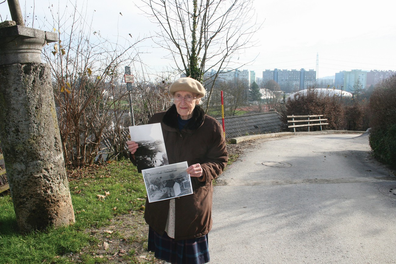 Milena Zalokar (b. 1927) at the site of the former Italian–German border crossing set up right next to her home (Cesta Andreja Bitenca). She is holding up photos of the demolition of her home, and of the border crossing, 11 December 2018. Author: Božidar Flajšman.
