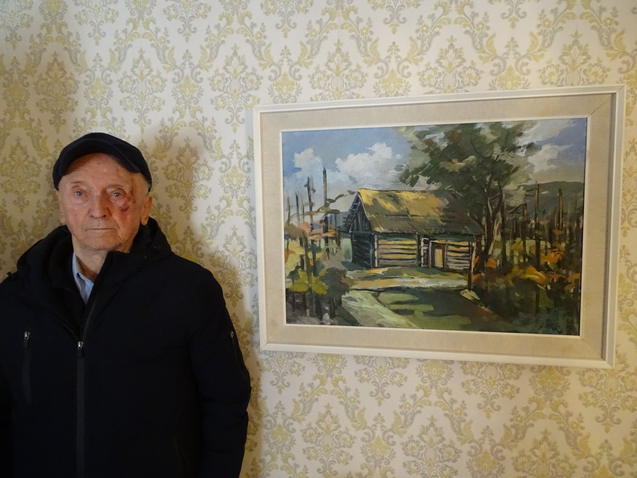 Jože Pirkovič (born 1934) next to a painting of his parents' vineyard cottage in Vajndol (Gorenje Vrhpolje). Italian soldiers used it for food storage. There was a bunker about 150m from the cottage; it was partly dug into the ground, was made of wood, and covered with soil around the rim. They had to cut down vineyards along the route of the fortified border. Jože's father made an arrangement with the Italian commander, so he did not have to cut down the vineyard; instead, he removed the stakes and fastened the vines to the ground. Author: Blaž Štangelj.