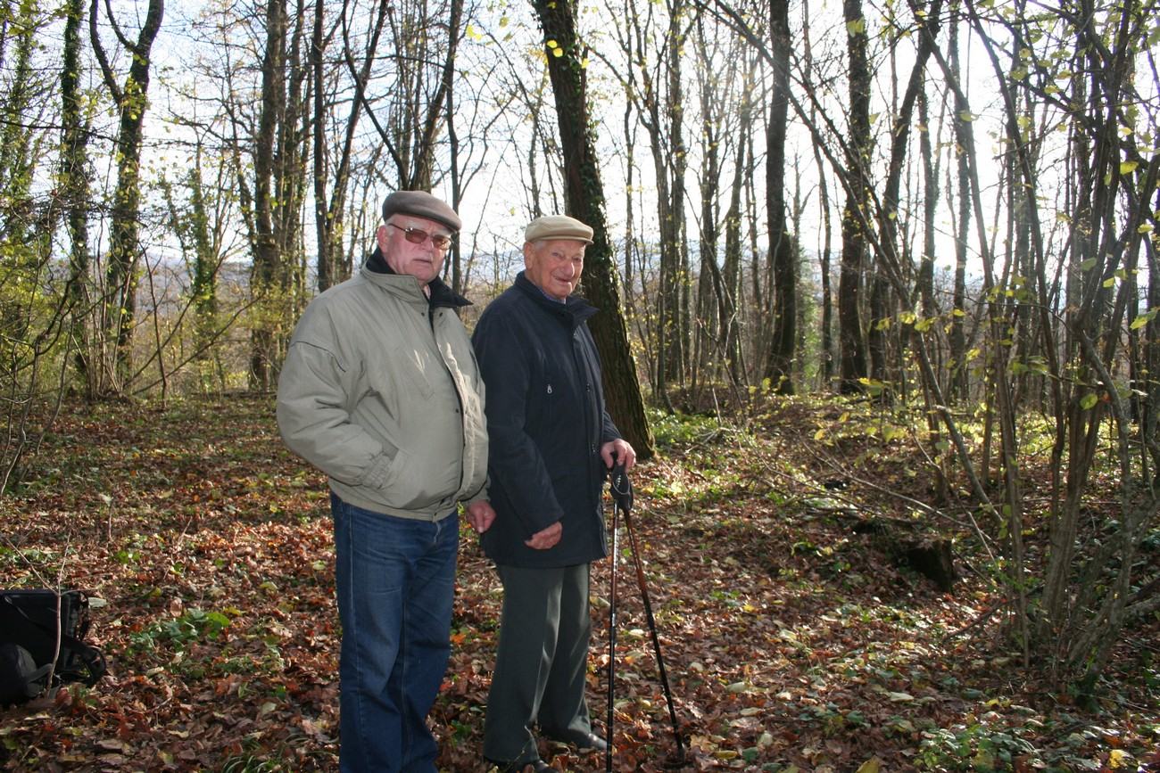 Slavko Franko and Stanko Kušljan next to the remains of Italian firing trenches at the village of Imenje pod Gorjanci near Šentjernej. Stanko (born 1919) gave a detailed description of how on one occasion, in broad daylight, his Cankar Brigade drove the Italians away from these positions and crossed the barricade of the border between the NDH and Italy. Author: Božidar Flajšman.