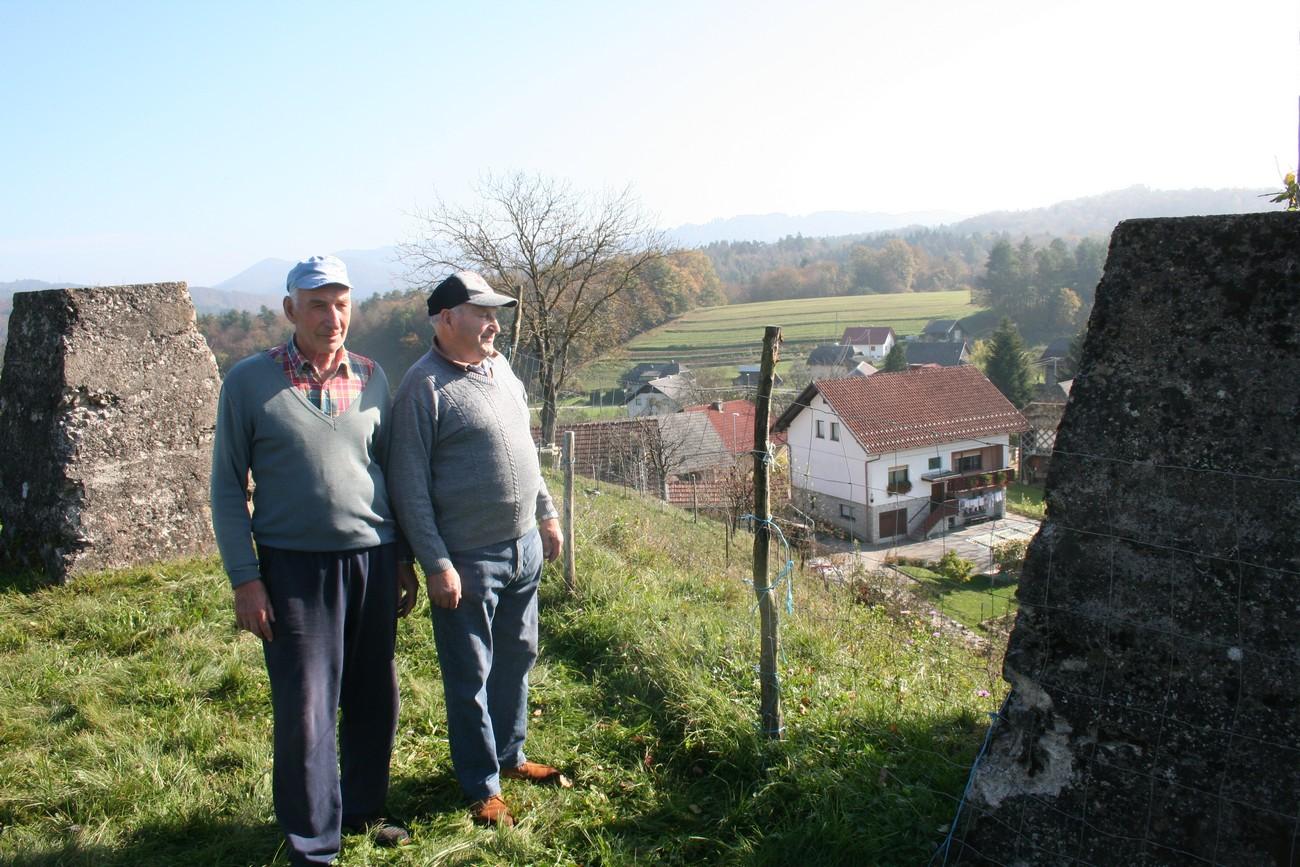 Marjan Zaman in Rafael Rafko Blažič ob betonskih temeljih nemškega stražnega stolpa v Hinjcah nad Krmeljem. Ob stražnem stolpu so Nemci zgradili tudi bunker in izkopali strelske jarke. V ozadju se vidi obnovljena kmetija Marjana Zamana, ki so jo Nemci porušili, ker je bila v obmejnem pasu. Marjana, ki je bil takrat otrok, pa so skupaj z družino, tako kot vse druge ob nemški meji, izgnali v Nemčijo. Avtor fotografije: Božidar Flajšman.