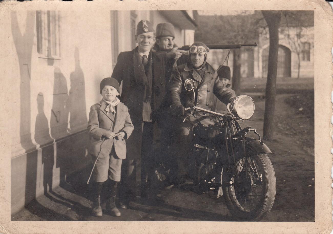Jože Vidič kot otrok (v ospredju), za njim Imre Csanádi z vojaško kapo, neznana oseba s puško v roki. Na motorju sedi Čurić, za njim stoji Dušan Živanov kot otrok. Fotografija je nastala 1. januarja 1944 v Sivcu (Bačka). Tam je bil v rejništvu pri družini Milosavljev, sestri Pavla in Marija pa pri družinah Majski in Pavko. Fotografijo hrani Jože Vidič.